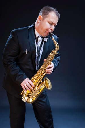 Portrait of Mature Expressive Caucasian Saxophonist Against Seamless Black Background. Vertical Compostiion