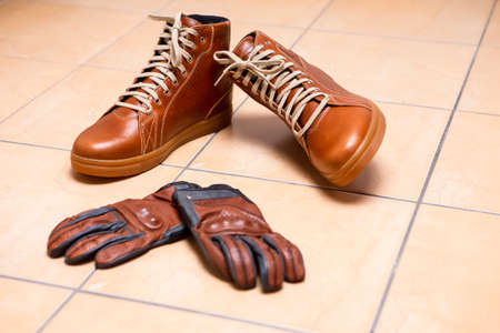 Motorcycling Relative Topics. Closeup of Protective Motorcyclist Leather Tan Sneakers Placed Indoors Along With Leather Gloves On Pale Tiles Floor. Horizontal Image Imagens