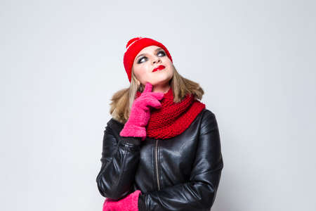 Winter Concepts. Portrait of Tranquil Caucasian Blond Girl In Warm Hat and Scarf Posing with Lifted Hands Against White. Horizontal Image