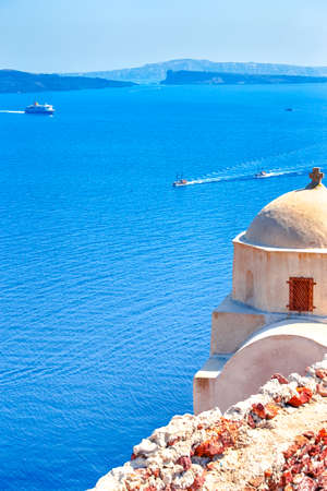 Sailing Boats Near Caldera Volcanic Slopes of Santorini Oia or Ia Village in Greece. With Traditional Pale Dome Orthodox Greek Church in Foregound.Vertical Image
