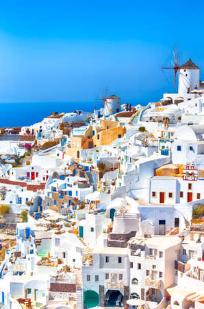 Greece Traveling. View of Greek Traditional Colorful Houses and Windmills of Oia or Ia at Santorini Island in Greece at Noon. Vertical Image Orientation