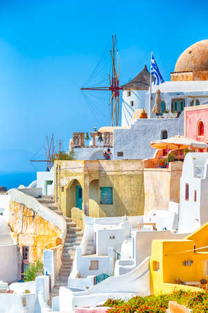 Greece Traveling. View of Greek Traditional Colorful Houses and Windmills of Oia or Ia at Santorini Island in Greece at Daytime. Vertical image Фото со стока
