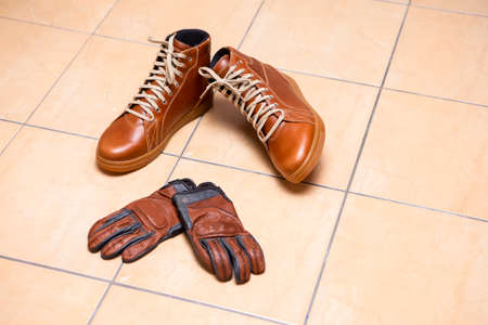 Motorcycling Relative Topics. Closeup of Protective Motorcyclist Leather Tan Sneakers Placed Indoors Along With Leather Gloves On Pale Tiles Floor. Horizontal Image composition