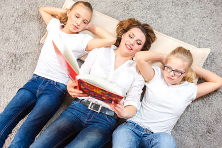 Family Ideas. Portrait of Caucasian Mother Reading a Book Together with Her Female Twins Laying on Floor Indoors. Horizontal Composition