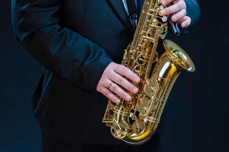 Closeup of hands of Professional Saxophonist Player Against Black. Horizontal image Orientation 版權商用圖片