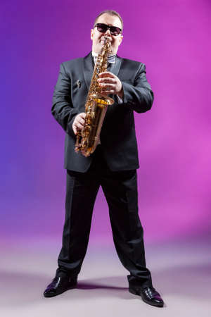 Musicians Concepts. Full Length Portrait of Mature Expressive Caucasian Saxophonist Against Colorful Background. Vertical Compostiion Stock Photo