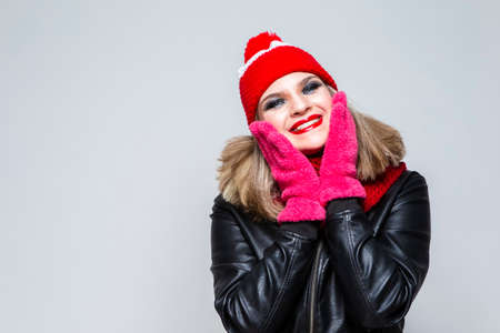 Winter Concepts. Portrait of Expressive Caucasian Blond Girl In Warm Hat and Scarf Posing with Lifted Hands Against White. Horizontal Image Composition Imagens