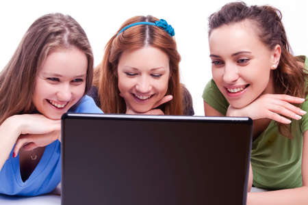 Youth Lifestyle. Portrait of Three Happy and Laughing Caucasian Girlfriends Working With Laptop Indoors. Horizontal Image