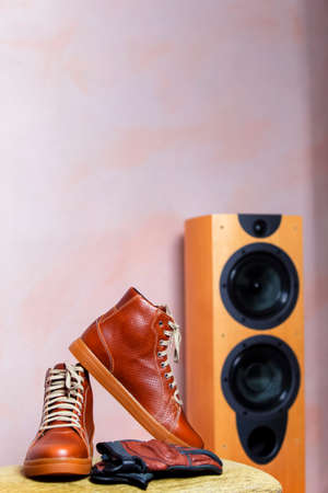 Motorcycling Concepts. Closeup of Protective Motorcyclist Leather Tan Sneakers Placed Indoors Along With Leather Gloves Against Floorstanding Loundspeaker. Vertical Shot