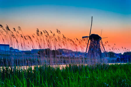 European Destinations. Traditional Romantic Dutch Windmill in Kinderdijk Village in the Netherlands At Dusk. With Large Number of Mosquitos in frame. Horizontal Shot