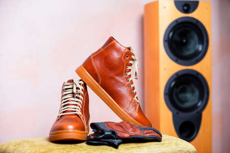 Closeup of Protective Motorcyclist Leather Tan Sneakers Placed Indoors Along With Leather Gloves Against Floorstanding Loundspeaker. Horizontal Shot Фото со стока