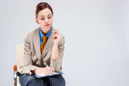 Portrait of Positive and Smiling Gleeful Woman in Blue Shirt and Tie. Making Notes with Notepad While Sitting in Chair. Horizontal Image