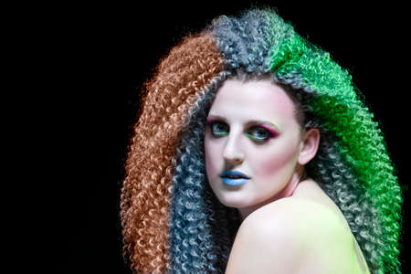 Creative Ideas. Caucasian Girl With Frizzy Colorful Hair and Artistic Eyes Makeup. Posing Against Black. Horizontal Image