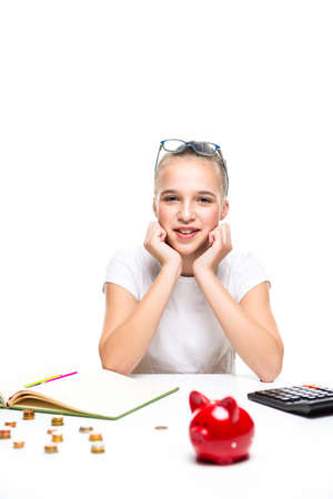 Children Frugal Concepts. Blond Teenage Girl Posing With Coins and Moneybox. Calculating Income With Calculator For Savings. Vertical Image Composition