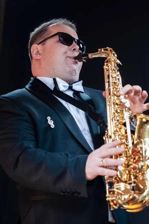 Portrait of Passionate and Extravagant Caucasian Saxophonist in Dark Suit Posing in Sunglasses Against Black. Vertical Image