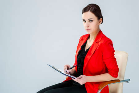 Portrait of Positive Confident Female Enterpreneur Posing in Red Blazer And Notepad While Making Notes Against White. Horizontal image 스톡 콘텐츠