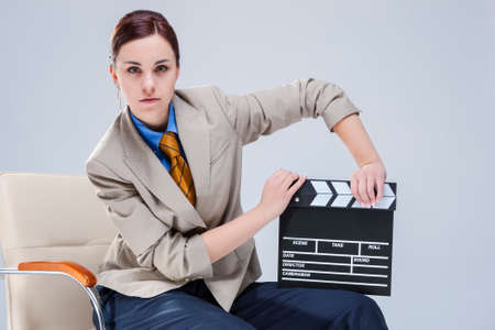 Portrait of Brunette Caucasian Woman in Shirt and Tie Posing in Chair with Actioncut. Horizontal Image Composition Stockfoto