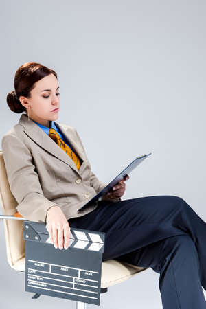 Filmmaking and Movie Concepts. Portrait of Professional Female Film Director Posing with Actioncut. Sitting in Chair with Notepad.Vertical Image Stockfoto