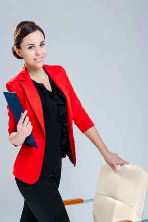 People in Business. Portrait of Smiling Female Enterpreneur Posing in Red Blazer And Notepad  Against White. Vertical Composition 스톡 콘텐츠