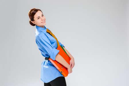 Portrait of  Gleeful Caucasian Businesswoman Posing with Colorful Folders In Studio. Horizontal Shoot