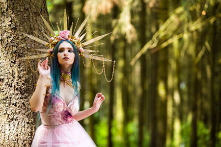 Costume Play.  Sensual Magnificent Crowned Forest Nymph with Flowery Golden Crown Posing in Summer Forest Against High Tree Stem. Horizontal Image