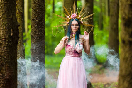 Costume Play Concepts. Sexy and Sensual Crowned Forest Nymph with Flowery Golden Crown Posing in Smoky Summer Forest Against High Trees. Horizontal Shoot