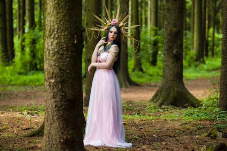 Costume Play Concepts. Sexy and Sensual Crowned Forest Nymph with Flowery Golden Crown Posing in Empty Summer Forest Against High Trees. Horizontal Image Composition