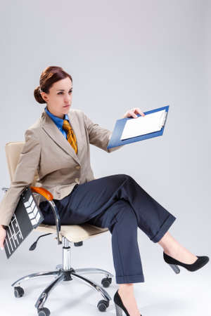 Filmmaking Concepts. Portrait of Confident Professional Female Film Director Posing with Actioncut. Pointing with Notepad While Sitting in Chair.Vertical Image