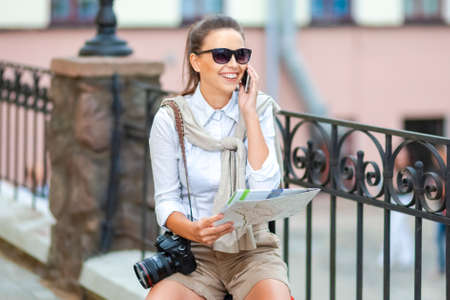 Laughing Fashionable Caucasian Woman in Sunglasses With Photo camera and Road Map Speaking On Cellphone Out in The City. Horizontal Image