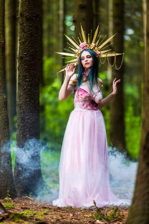 Sexy and Sensual Crowned Forest Nymph with Flowery Golden Crown Posing in Smoky Summer Forest Against High Trees. Vertical Image Composition