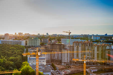 New Construction Site with Building Cranes Against Sunny Sky. Horizontal Image Orientation