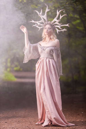 Beautiful Girl Posing With Artistic Deer Horns  In Summer Forest Near High Tree. Wearing Light Dress for Forest Nymph Concept. Art Photography. Vertical Image Banque d'images