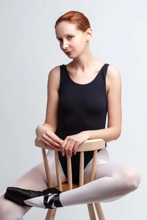 Portrait of Female Ballet Dancer in Body Suit Sitting On Chair and Listening Music on Headphones. Against White Background. Horizontal Image Composition