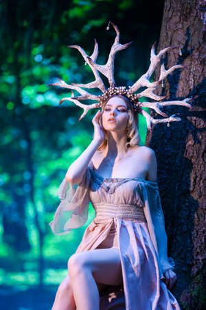 Beautiful Girl Posing With Artistic Deer Horns  In Summer Forest Near High Tree. Wearing Light Dress for Forest Nymph Concept. Art Photography. Vertical Image Orientation Banque d'images