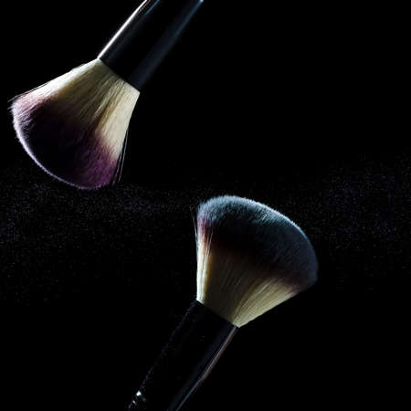 Cosmetics Concepts And Ideas. Macro Shot of Two Professional Makeup Brushes With Colorful Eyeshadows Explosion. Against Black Background. Vertical image Composition