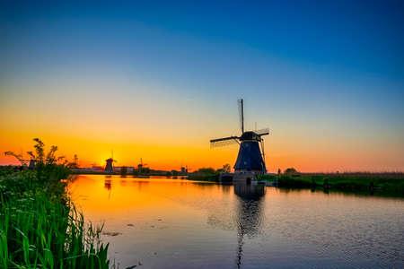 Traditional Romantic Dutch Windmills in Kinderdijk Village in the Netherlands During Golden Hour. Horizontal Shoot