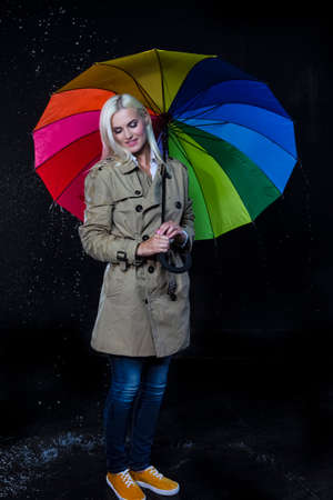 Full Length Portarit of Positive Caucasian Blond Female Posing with Colorful Umbrella Under The Rain Droplets.Vertical Composition