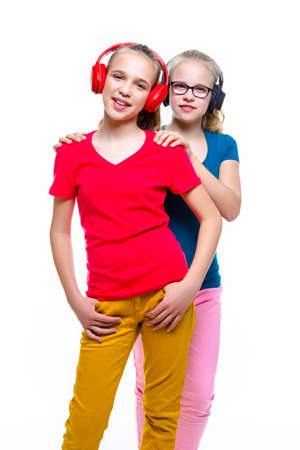 Positive Twins Teenager Girls Posing With Wireless Headphones On White Background. Vertical Image