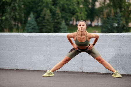 Sport Ideas. Caucasian Female Runner Doing Stretching Exercises Outdoor. Horizontal Image