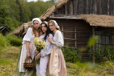Art Photo of Three Lovely Country Girls with Basket of Homemade Bread and Flowers. Posing Together in Countryside Environment Outdoor.Horizontal Image Orientation Foto de archivo