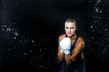 Portrait of Professional Active Female Boxer Posing with White Gloves in Aqua Studio Against Black Background. Horizontal Shoot Banque d'images