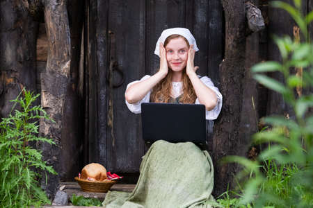 Natural Portrait of Smiling Country Redhaired Girl Working with Laptop in Village Outdoors. Horizontal image