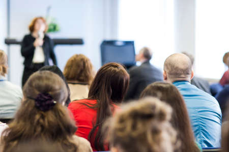 Professional Female Lecturer Speaking In Front of the Group of People At The Conference. Horizontal Image Composition Imagens