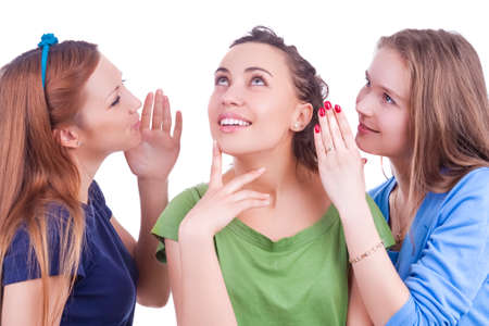 Three Young caucasian Girlfriends Sharing Their Secrets Whispering to Ears.Isolated Over White Background. Horizontal image