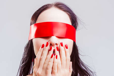 Portrait of Mature Caucasian Brunette Woman Posing with Red Ribbon Blinder on Eyes with Passionate Expression.Horizontal Image Composition