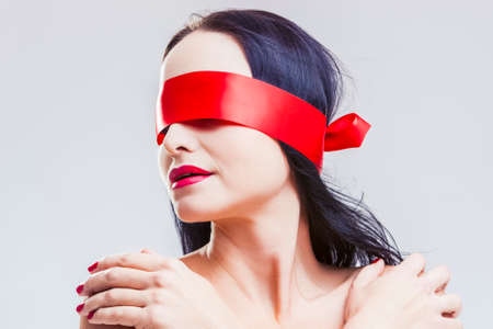 Sensual Mature Caucasian Brunette Woman Posing with Red Ribbon Blinder on Eyes with Calm Alluring Expression.Horizontal Composition