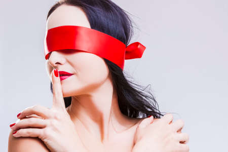 Sensual Mature Caucasian Brunette Woman Posing with Red Ribbon Blinder on Eyes with Point Finger Near Lips.Horizontal Image
