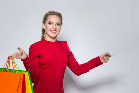Positive Caucasian Girl Posing With Plenty of Colorful Shopping Bags and Bank Card. Horizontal image