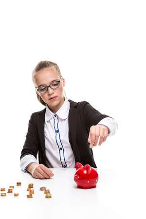 Portrait of Teenage Girl in Dark Jacket Putting Coin Into The Piggybank For Savings. Vertical Image Reklamní fotografie
