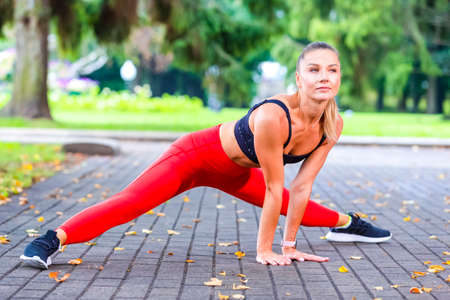 Sexy Caucasian Female Runner During Forward Stretching Body Exercises Outdoors At Daytime. Horizontal Image